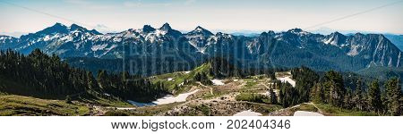 Tatoosh mountain range panorama in Mount Rainier National Park. Walking trails in the foreground lead to the range viewpoint.