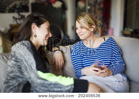 Two Peoples relations. Two girls are speaking with emotions sitting on sofa