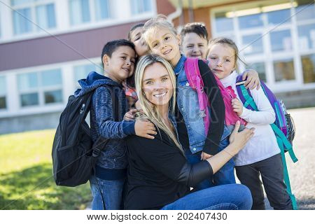 A Group of students outside with teacher at school standing together