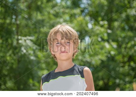 Portrait of an annoyed boy on a tree with green leaves background