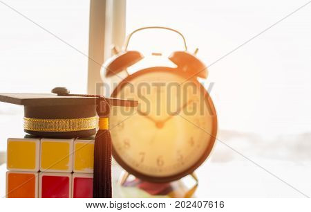 Graduation cap Put on Ball with clock and Rubik cube Tennis is a racket sport can be played individually against single opponent Sports competition success concept
