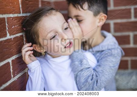 A Little boy and girl whispers a secret.