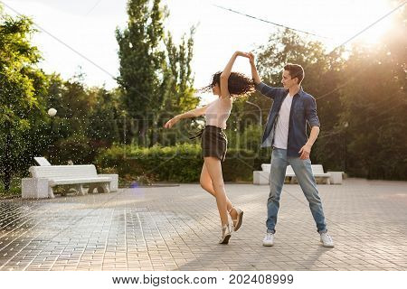 Teens dancing in the city park. Couple in love. Romantic first date. Carefree and free youth.
