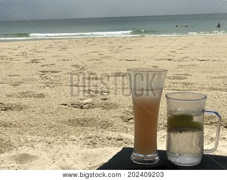 Orange Fruit cocktail on a deckchair on wet sand beach and see view