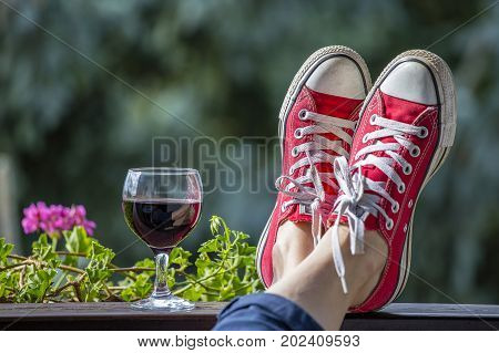 Red sneakers on the legs of a woman and a glass of wine against the background of nature close up