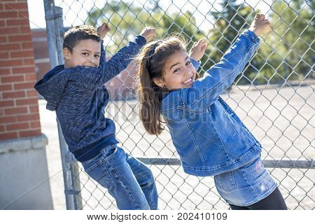 two childs at elementary school outside having fun