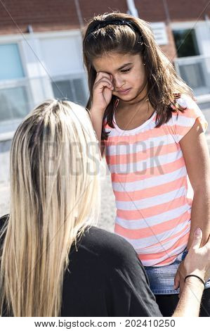 A teacher consoling girl on a schoolyards