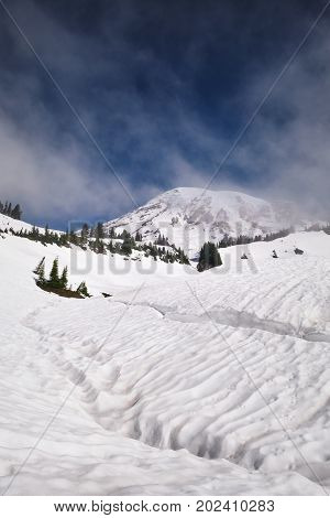 Mount Rainier with a snow-covered lake in the foreground during June