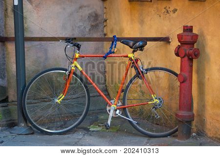 Old orange and yellow bicycle chained to avoid stealing it