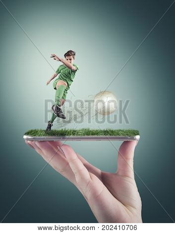 Hand holding a smartphone which displays a soccer match on the touch screen. Soccer player shooting the ball.