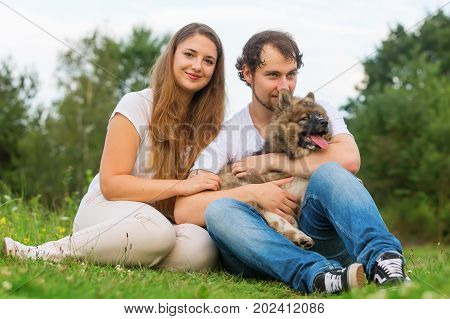 portrait of a young couple who is sitting with an elo puppy on the grass