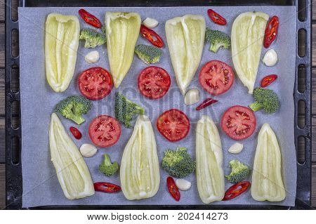 Green and red peppers tomatoes broccoli and garlic prepared on baking trays for baking in the oven. Top view close up