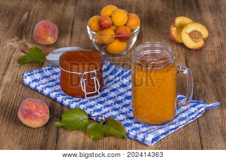 Healthy eating food dieting and vegetarian concept - smoothie from apricot and peach in mug and jam close up. Fresh apricot and juice on wooden background