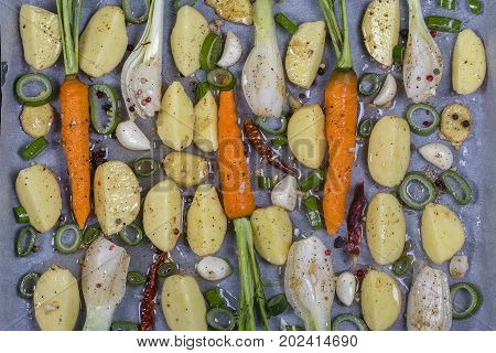 Young potatoes carrots onion pepper garlic prepared on baking trays for baking in the oven. Top view close up