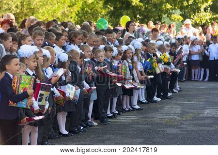 Adygea Russia - September 1 2017: children with bouquets of flowers enrolled in the first class with teachers and high school students on the school's solemn line in the day of knowledge