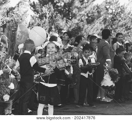 Adygea Russia - September 1 2017: happy children enrolled in the first class with gifts in the hands of teachers and high school students on the school line in the day of knowledge black and white photo