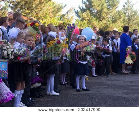 Adygea Russia - September 1 2017: happy children enrolled in the first class with gifts in their hands on the school's solemn line in the day of knowledge
