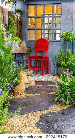 Relaxing area with red chair in cozy garden.