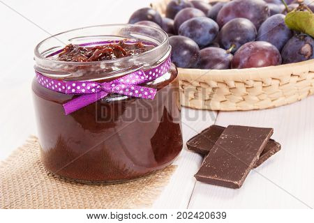 Plum Marmalade Or Jam In Glass Jar, Fruits In Wicker Basket And Chocolate, Sweet Dessert Concept
