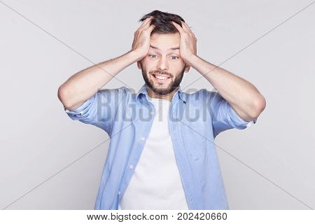 Desperate stressed young Caucasian bearded man looking down in terror and shock keeping mouth wide open and eyes popped holding head frightened while forgetting to make an important report.