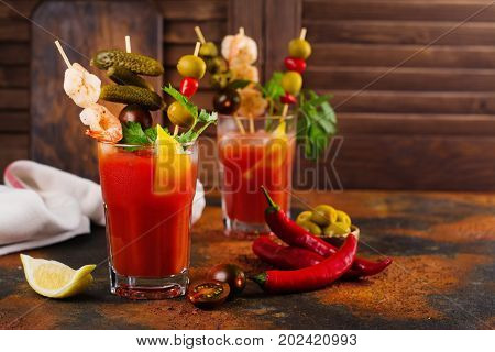 Homemade spicy vodka bloody mary cocktail with shrimps and pickled cucumbers
