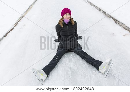 Ice skating woman sitting on the ice and smiling.