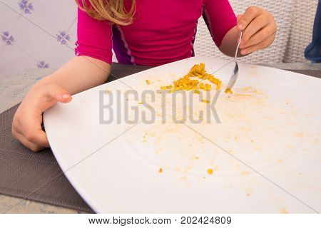 Little Child Eating And Finishing Big Plate Of Paella