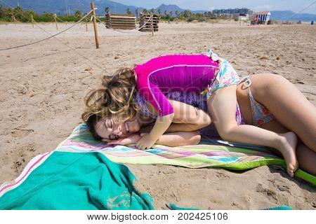 Little Child Lying On Mother Over Towels At Beach