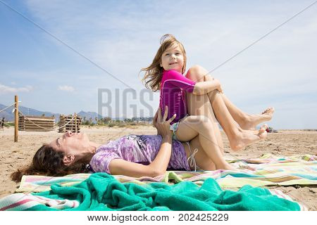Little Child Sitting On Woman Holding Her Legs At Beach