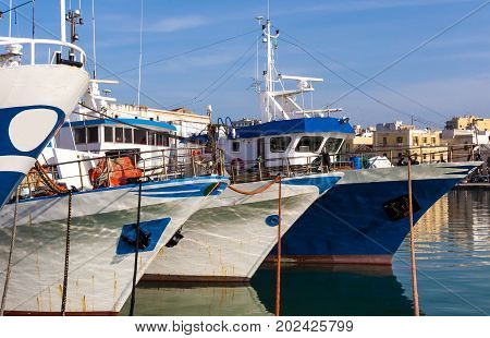Fishing motorboats tied to mooring cleats of a port