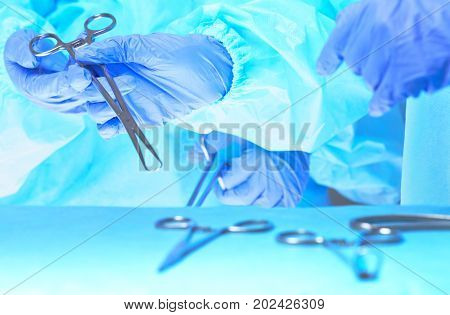 Close-up of of surgeons hands at work in operating theater toned in blue. Medical team performing operation