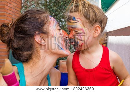 Mother And Little Daughter With Painted Face Kissing