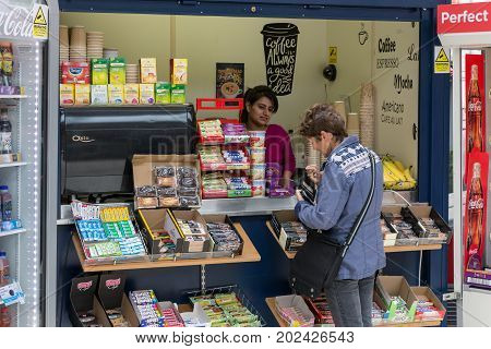 WINDSOR ENGLAND - JUNE 09 2017: Woman buying sweets in kiosk of Railway station near Windsor Castle.