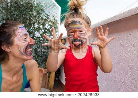 Woman And Little Child With Painted Face Making Grin
