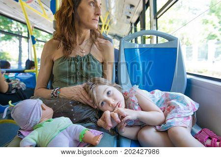 Little Girl Lying On Mother Legs On The Bus