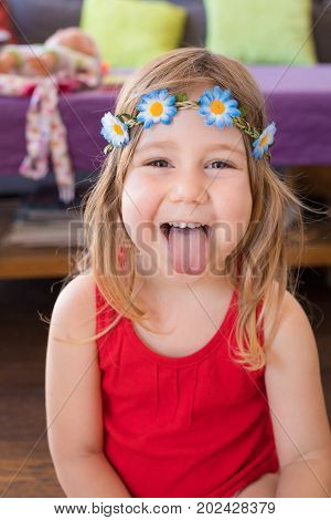 Portrait Of Hippie Little Girl Sticking Out Tongue