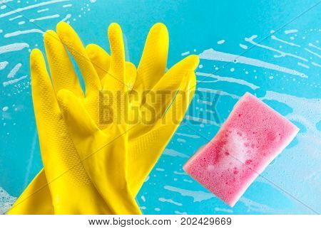 Cleaning concept gloves and sponge in foam on a blue background
