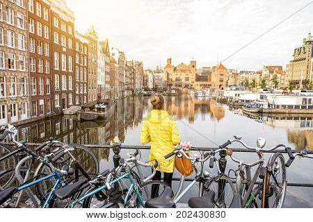 Young woman in yellow raincoat enjoying morning view on the beautiful cityscape view in Amsterdam
