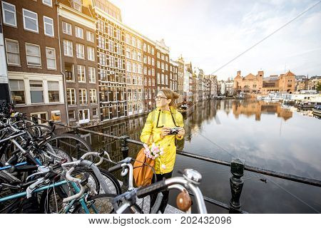 Young woman in yellow raincoat with photo camera enjoying morning view on the beautiful cityscape view in Amsterdam