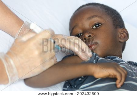 Sad African boy is worried about getting an injection for his health as a vaccination. A nice close-up of a little black African ethnicity boy getting a medical injection as a vaccination. Symbol for African illness fighting. Black boy as a patient for a