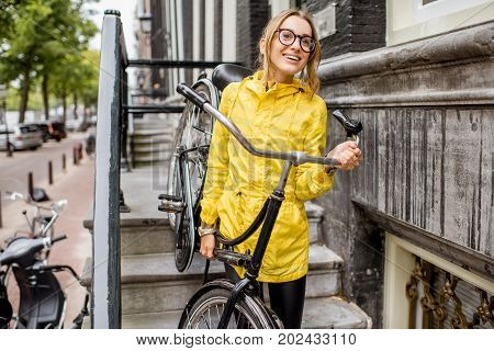 Young woman in yellow raincoat taking down a bicycle on the stairs near the beautiful residential house in Amsterdam