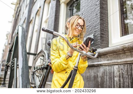 Young woman in yellow raincoat standing with a bicycle and phone on the stairs near the beautiful residential house in Amsterdam