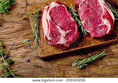 Raw Meat Ribeye Steak With Seasoning  On Dark Wooden Background