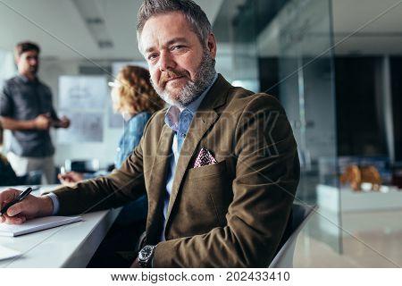 Businessman sitting in board room. Horizontal shot of mature businessman sitting in meeting room during presentation.