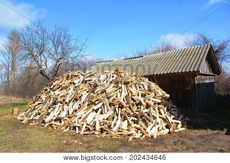 Pile of chopped wood. Pile of firewood against old wooden rural house.