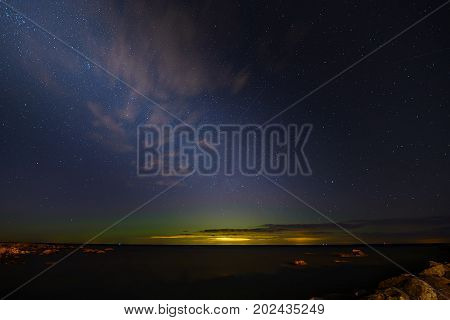 Aurora Boralis and milky way on a Bltic sea.