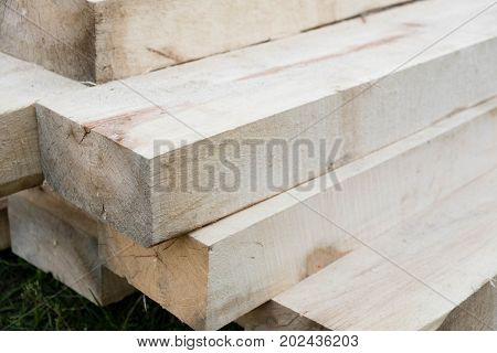 Stack of new wooden studs at the lumber yard. Wood timber construction material. Shallow depth of field effect