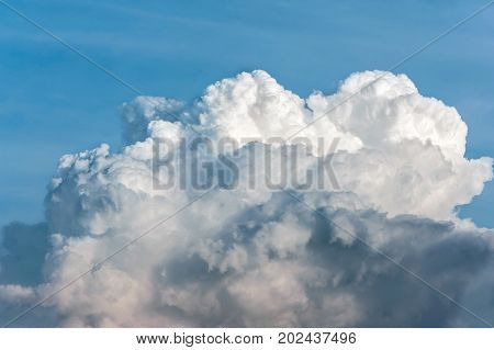 White cumulus congestus clouds on blue sky background. Vibrant outdoors horizontal image with copy space.