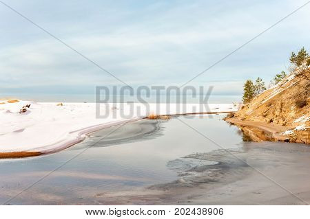 Landscape with melting in springtime on Baltic sea. Thaw river. Outdoors. Latvia.