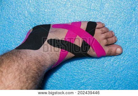 Kinesiology Therapeutic Elastic Sports Tape. Apply treatment on the left foot of the man after the accident. poster